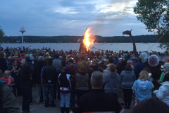 The ceremonial fire begins in the heart of Eagle Habor to a background of music and the crowd cheering.