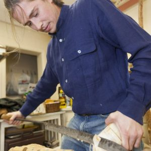 An image of Luke carving a wooden shoe.